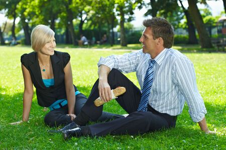 Young businesspeople sitting on grass and having lunch in a park summertime. Stock Photo - 6220683