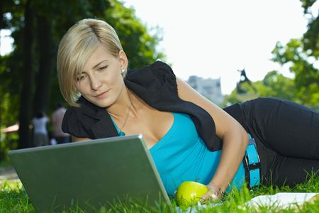 Young businesswoman lying in grass with in park, using laptop compuer. photo