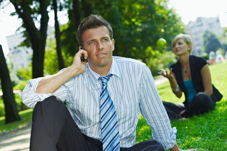 Businessman sitting in grass in park, talking on mobile. Busineswoman relaxing in the background. photo