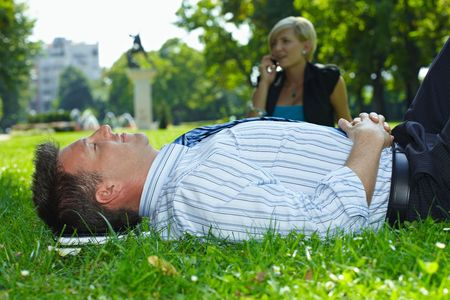 Businessman resting in grass in park, busineswoman talking on mobile in the background. Stock Photo - 6220068