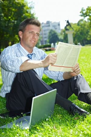 Relaxed businessman sitting in grass beside laptop computer, reading newspaper. Stock Photo - 6220694