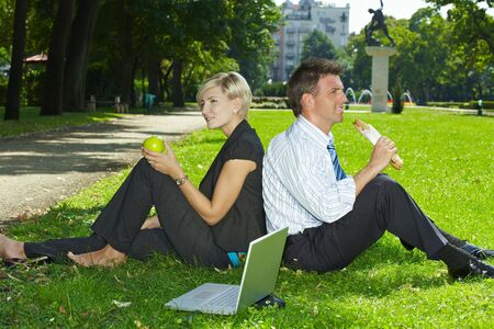 Young businesspeople sitting in grass and having lunch in a park summertime. Stock Photo - 6220686