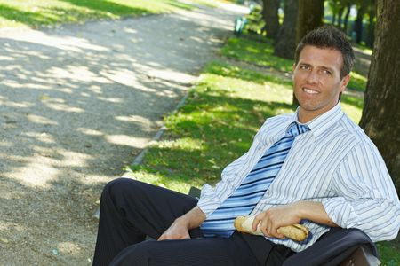 Casual businessman sitting on bench in park holding sandwich, smiling. Stock Photo - 6220695