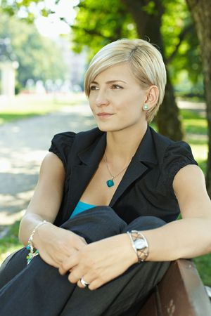 Portrait of young businesswoman sitting on beanch in sunny park, smiling. Stock Photo - 6220688