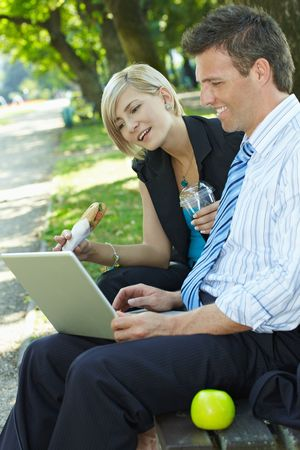 Young businesspeople sitting on bench in park having luch and looking at laptop computer. Stock Photo - 6220057