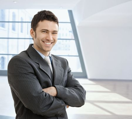 Happy businessman standing with arms crossed in office lobby, looking at camera, smiling.  photo