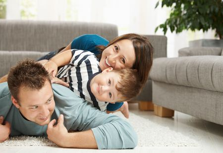 Happy family playing at home, lying heaped on floor in living room. Stock Photo