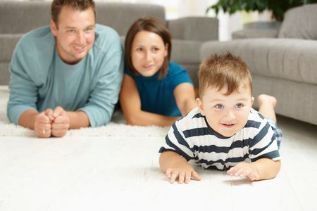 Happy family lying on floor in living room. Selective focus on little boy. Stock Photo - 6220718