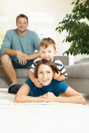 Happy mother and son lying on carpet at home, father watching from background. Stock Photo - 6220702