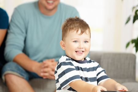 Portrait of happy little boy at home with his parents in background. Selective focus on child. photo