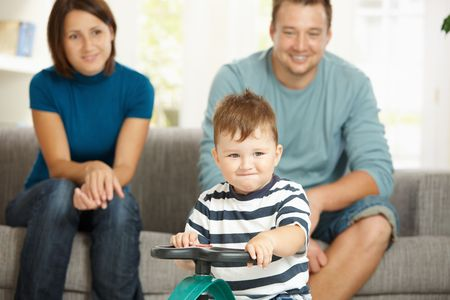 Happy little boy driving toy car his parents sitting on couch in background. Selective focus on child. Stock Photo - 6220713
