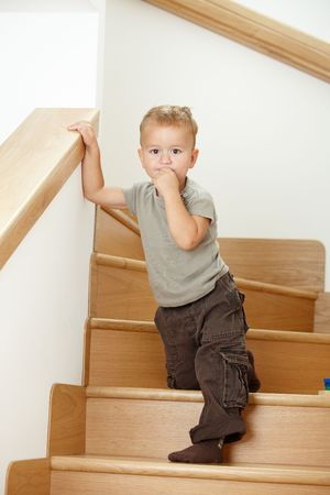 hand rail: Worried little boy standing on stairs, leaning on hand rail.