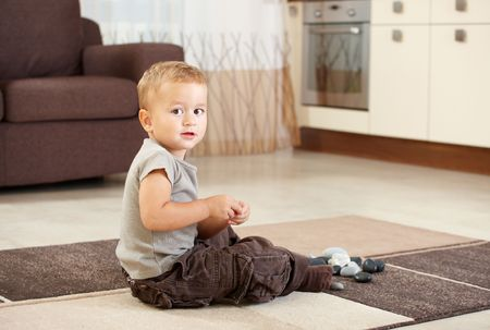 Little boy sitting on carpet in kitchen playing with pebbles. photo
