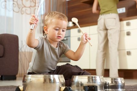 play of color: Little boy sitting on carpet in kitchen playing with cooking pots, mother preparing food in background. Stock Photo