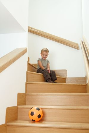 Happy little boy sitting on stairs, looking at ball, laughing.  photo