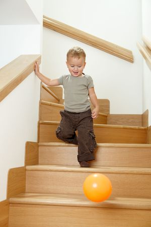 Happy little boy going down stairs after orange ball. photo