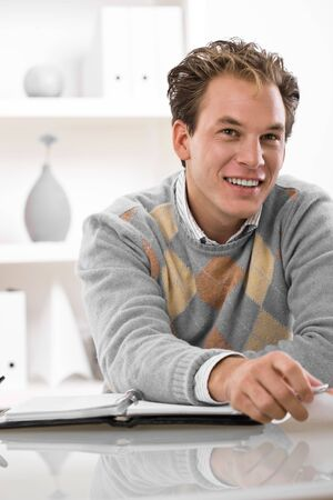 Happy young man working at desk at home. photo
