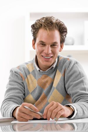 Happy young man writing on desk at home, smiling. photo