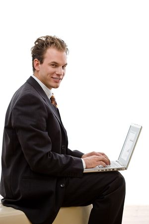businesswear: Businessman working on laptop computer, isolated on white background.