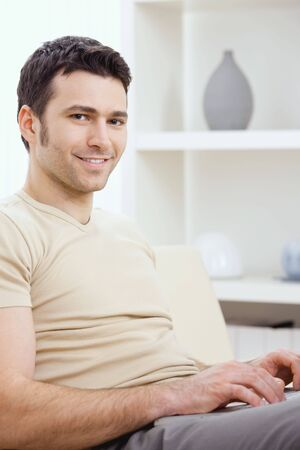 Happy young man in t-shirt sitting on sofa at home, working on laptop computer, smiling. Stock Photo - 6223939