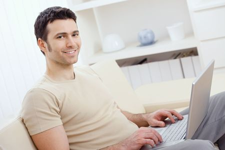 telecommuting: Happy young man in t-shirt sitting on sofa at home, working on laptop computer, smiling. Stock Photo