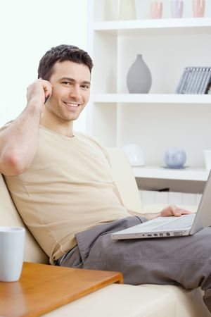 Young man sitting on sofa and teleworking from home. Stock Photo - 6224477