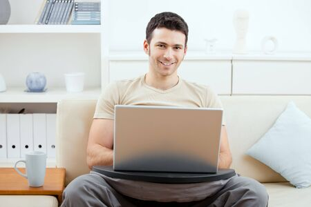 Casual man wearing beige t-shirt using laptop computer at home, sitting on couch, looking at camera, simling. photo