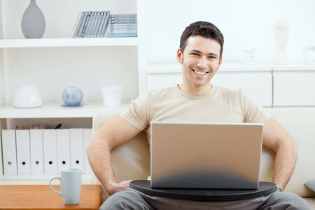 teleworking: Happy man wearing beige t-shirt using laptop computer at home, sitting on couch, looking at camera, simling.