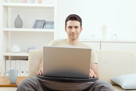 Happy young man sitting on couch at home using laptop computer, smiling. photo