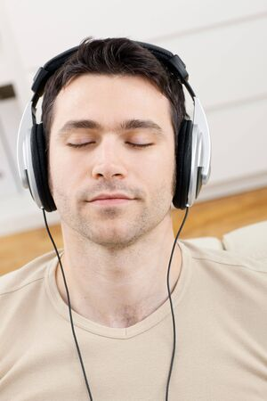 Casual man listening music with headphones at home, relaxing with closed eyes. photo
