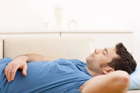 only 1 man: Young man in blue t-shirt sleeping on couch in living room.