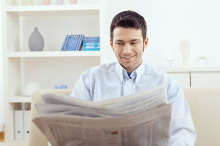 Happy young man sitting on couch reading newspaper at home, smiling. Stock Photo - 6223877