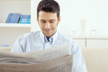 Handsome young man reading newspaper at home. photo