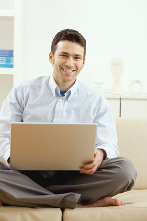 Happy young man sitting on couch and working on laptop computer at home, smiling. Stock Photo - 6223997