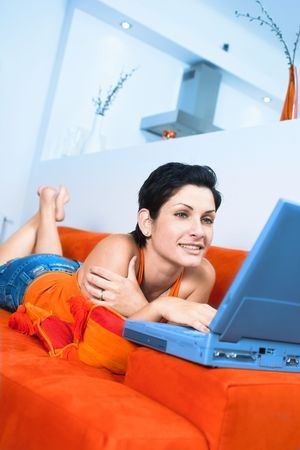 outwork: Young women is resting on the couch and surfing the internet on her laptop computer.