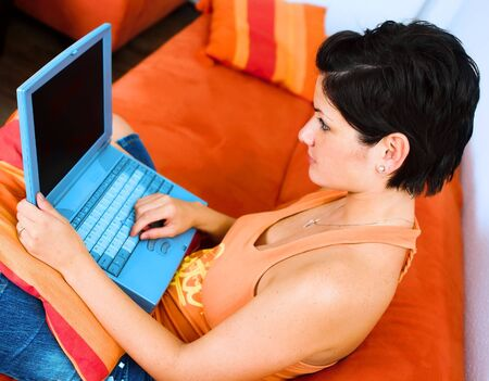 sinecure: Young women is sitting on the sofa at home and using a laptop computer.