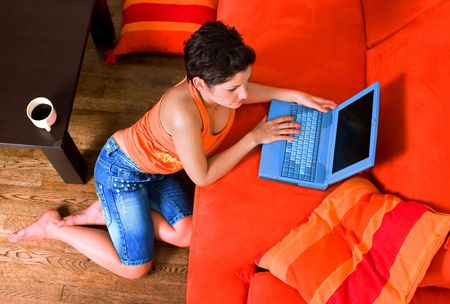 sinecure: Young women is lying on the couch at home and using a notebook computer. Stock Photo