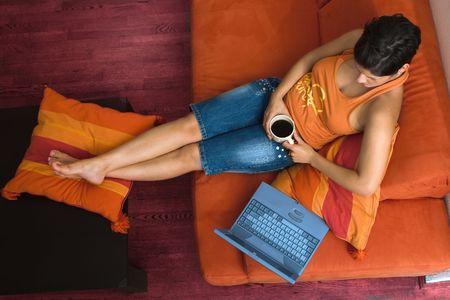 outwork: Las mujeres j�venes es descansar en el sof� y navega por internet en su equipo port�til.