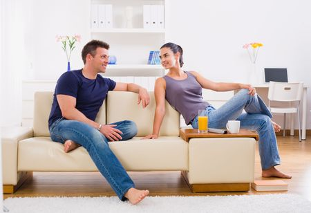 home comfort: Happy young couple sitting on sofa at home, smiling.