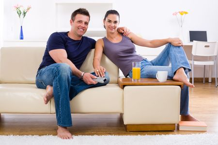 Happy young couple sitting on sofa at home, smiling. photo