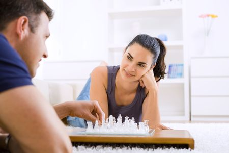 Young couple playing chess at home lying on floor. Selective focus placed on the woman. photo