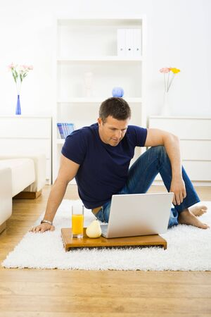 outworking: Casual young man working at home on his laptop, sitting on floor looking at screen.