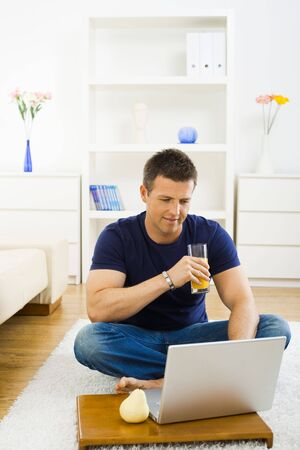 Casual young man using laptop computer at home, sitting at floor, drinking orange juice. Stock Photo