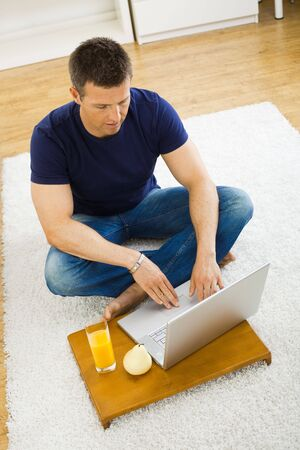 outworking: Casual young man using laptop computer at home, sitting at floor, looking at screen. High angle view. Stock Photo