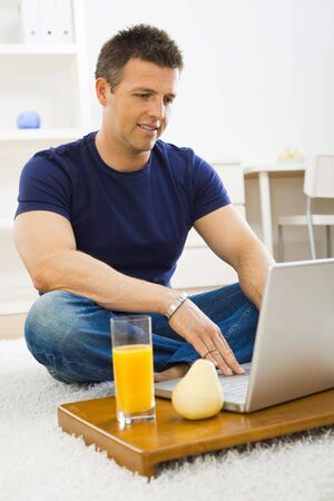 Casual young man using laptop computer at home, sitting at floor, looking at screen. Stock Photo