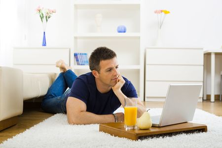 outworking: Casual young man working at home on his laptop computer, lying on floor and leaning on hand.