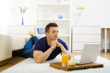 Casual young man working at home on his laptop computer, lying on floor, leaning on hands.