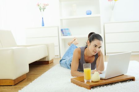 Young woman lying on floor at home and working on laptop computer, looking at screen. photo