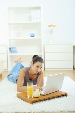 Young woman lying on floor at home and working on laptop computer, looking at screen. Stock Photo - 6235773