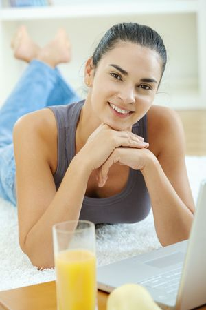 Happy woman lying on floor at home and working on laptop computer, smiling. Stock Photo - 6235828